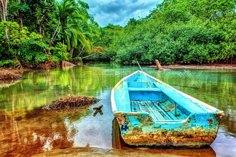 Old boat in tropical river, perfect place for fishing, exotic summer adventure, amazing nature of National Park of Costa Rica, Central America, stock photo