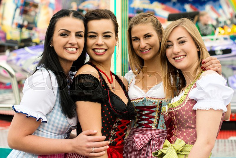 joyful young and attractive women at german funfair oktoberfest with traditional dirndl dresses. Black Bedroom Furniture Sets. Home Design Ideas