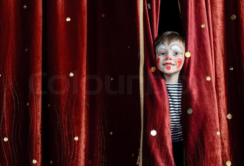 Young Boy Wearing Clown Make Up Peering Out Through Opening in Red Stage Curtains, stock photo