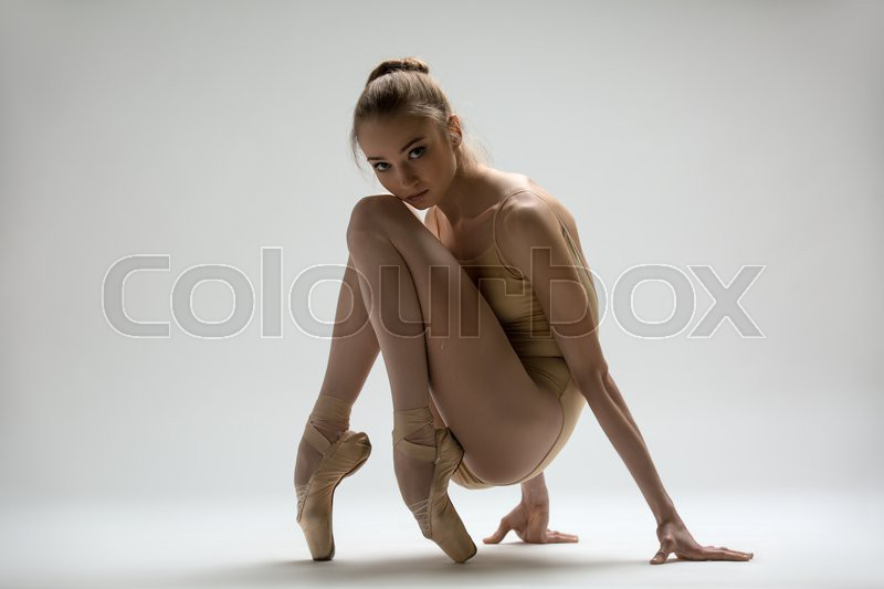Graceful ballerina in a solid swimsuit sitting at the floor with his hands on pointe in studio, stock photo