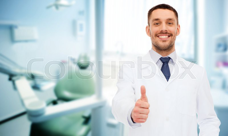 Healthcare, profession, stomatology and medicine concept - smiling male dentist showing thumbs up over medical office background, stock photo