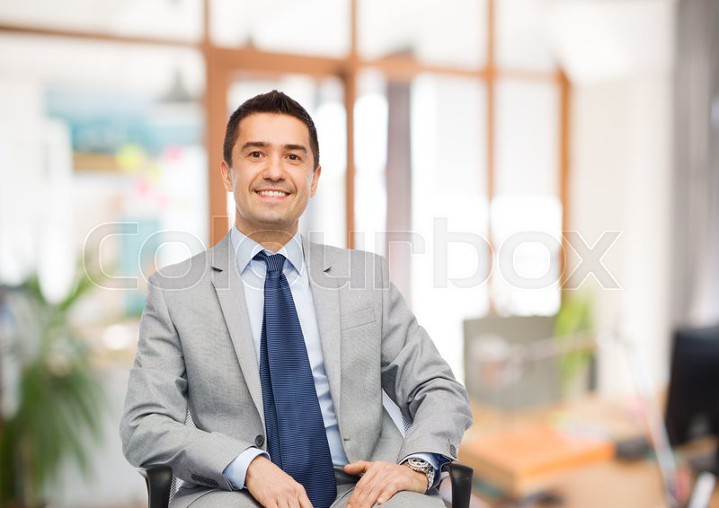 Business, people and office concept - happy businessman in suit sitting in chair over office room background, stock photo