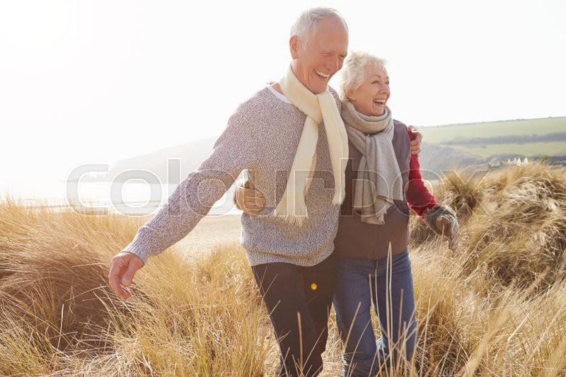Senior Couple Walking Through Sand Dunes On Winter Beach, stock photo
