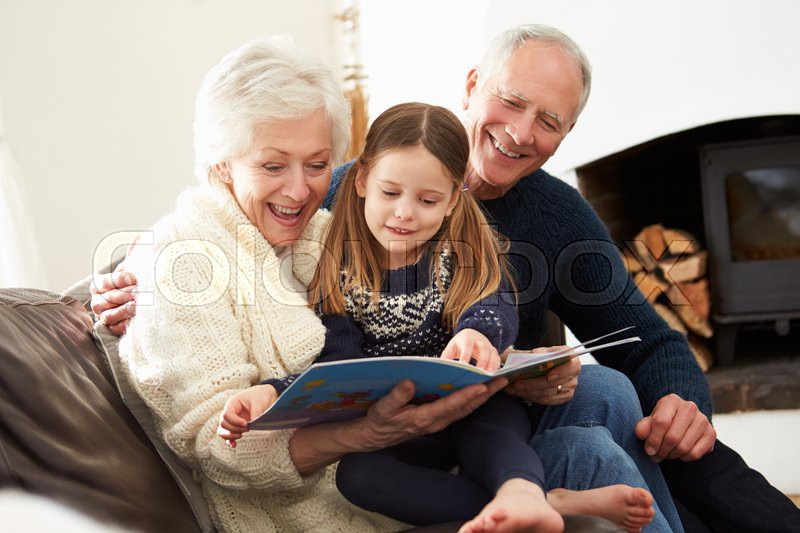 Grandparents And Granddaughter Reading Book At Home Together, stock photo