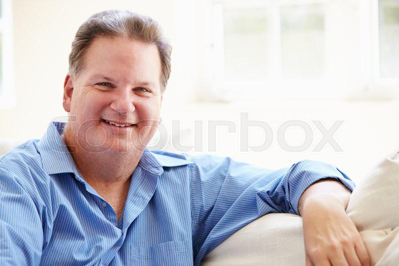 Portrait Of Overweight Man Sitting On Sofa, stock photo