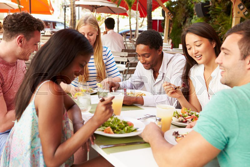 Group Of Friends Enjoying Lunch In Outdoor Restaurant, stock photo