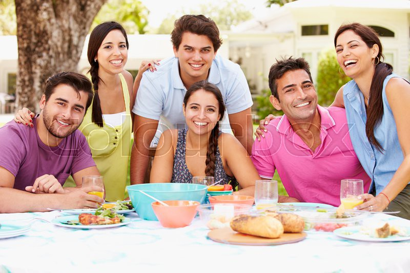 Group Of Friends Celebrating Enjoying Meal In Garden At Home, stock photo