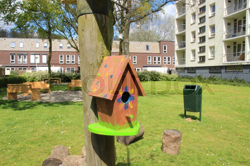 Selfmade striking bird house in the residential area with terraced house and an apartment building in spring in the village, stock photo
