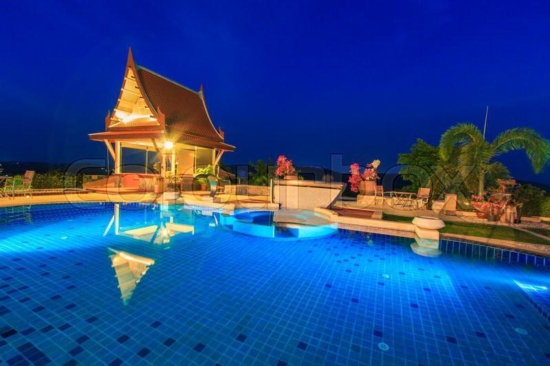 Modern resort with swimming pool at night, stock photo