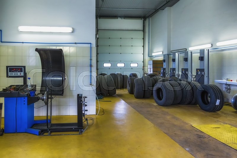 Truck tires or tyres repair shop service interior with wheel balancer, stock photo