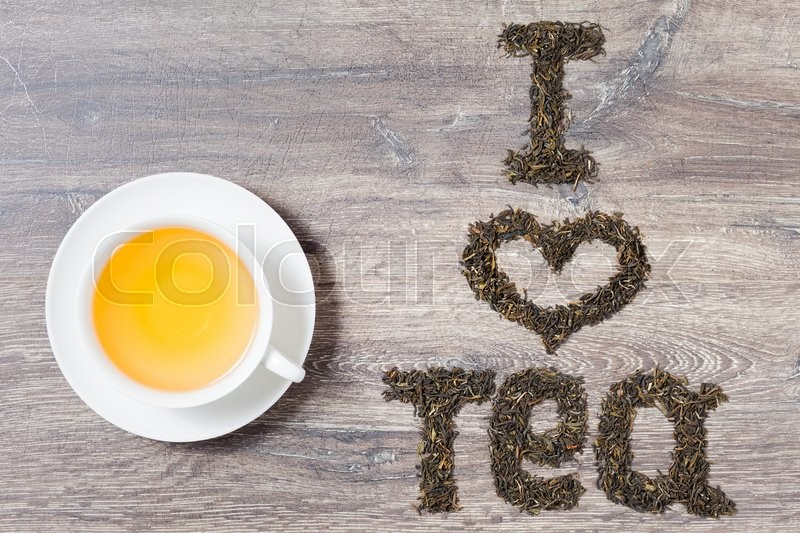 Words I love tea made of green tea leaves on wood background. Text on the right. A cup of tea on the left, stock photo