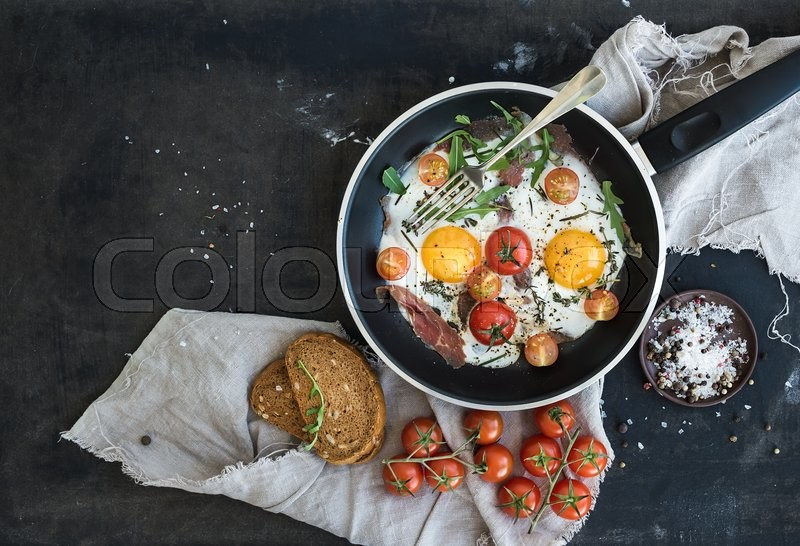 Pan of fried eggs, bacon and cherry-tomatoes with bread on dark table surface, top view, stock photo