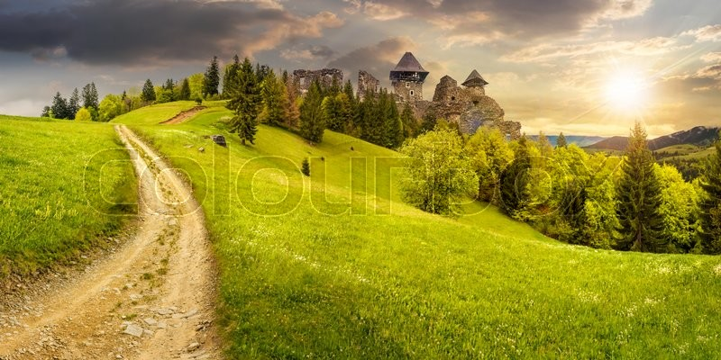 Composite mountain landscape. curve path to abandoned ruins of ancient fortress through green meadow on mountain hillside with forest in sunset light, stock photo