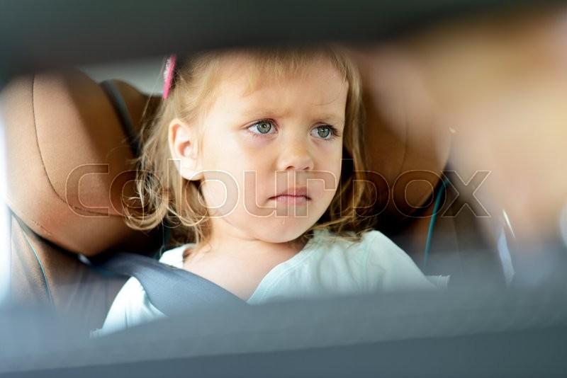 Sad little girl in the car seat, stock photo