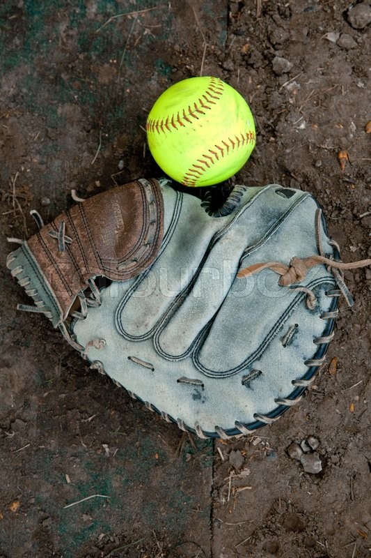 Softball Ball Lying on the Ground Near the Glove. Picture, Photo, stock photo