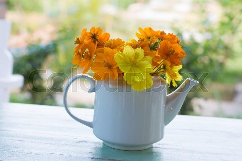 Bunch of yellow garden cosmos flowers bouquet in vase on wooden ...