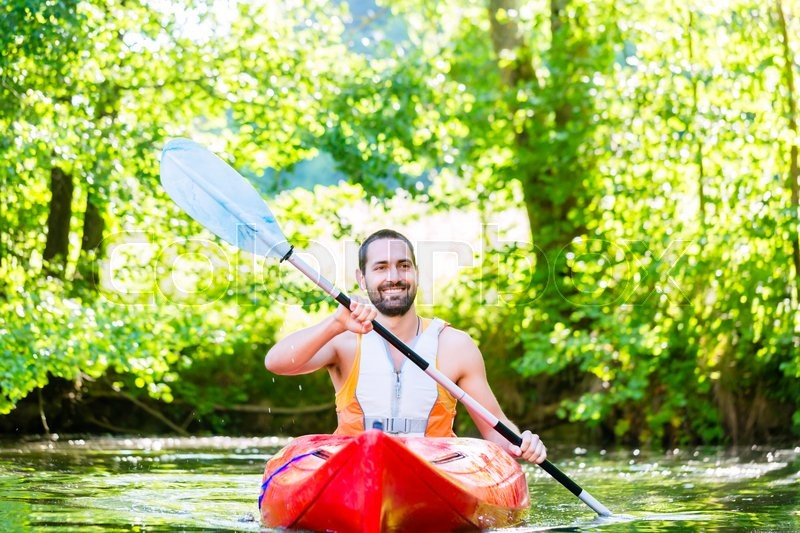 Man paddling with kayak on river for water sport, stock photo