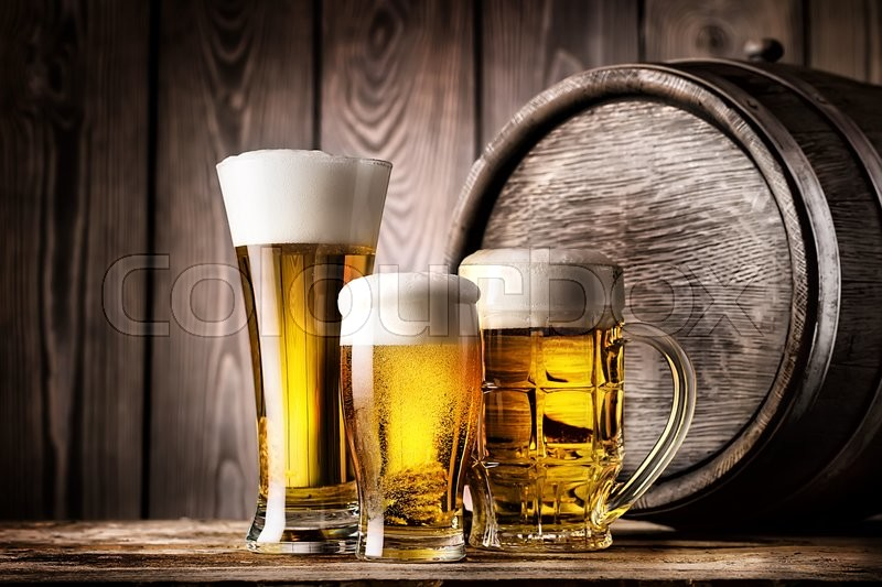 Two glasses and mug of light beer on a background of the old wooden barrels, stock photo