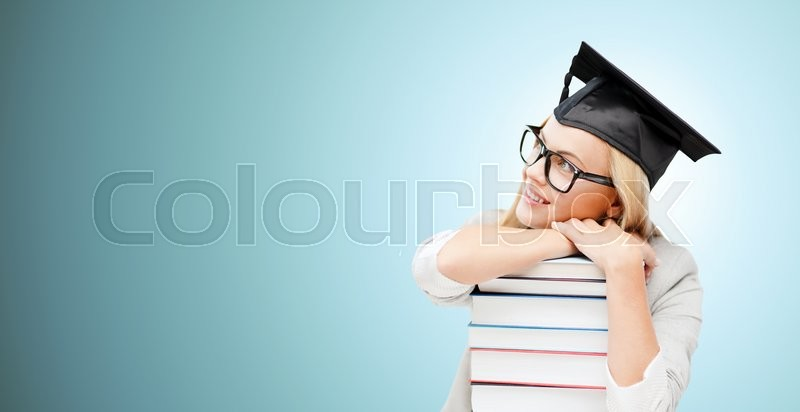 Education, happiness, graduation and people concept - picture of happy student in mortar board cap with stack of books daydreaming over blue background, stock photo