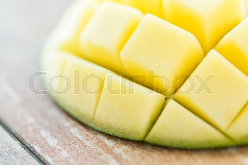 Stock image of 'fruits, diet, food and objects concept - close up of ripe mango slice on table'