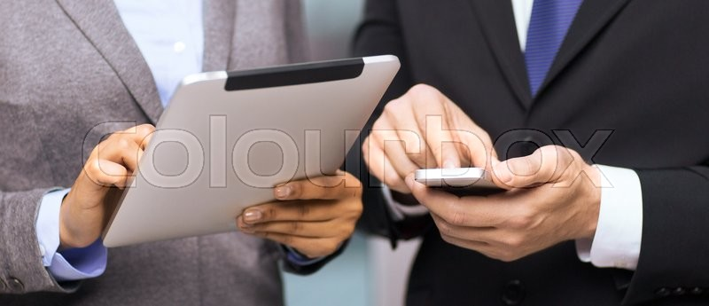 Business, technology, internet and office concept - businessman and businesswoman with smartphone and tablet pc computer in office, stock photo