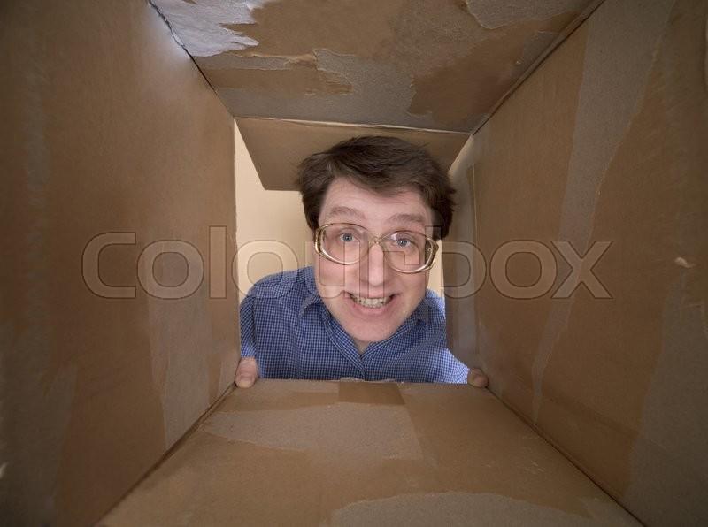 Man portrait on spectacles inside carton box, stock photo