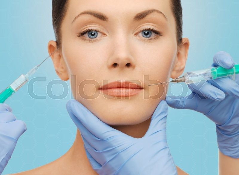 Plastic surgery, injections and beauty concept - beautiful young woman face and surgeon hands with syringes over blue background, stock photo