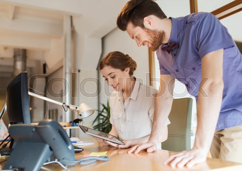 Business, startup and people concept - happy creative team with tablet pc computer in office, stock photo