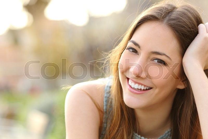 Woman smiling with perfect smile and white teeth in a park and looking at camera, stock photo