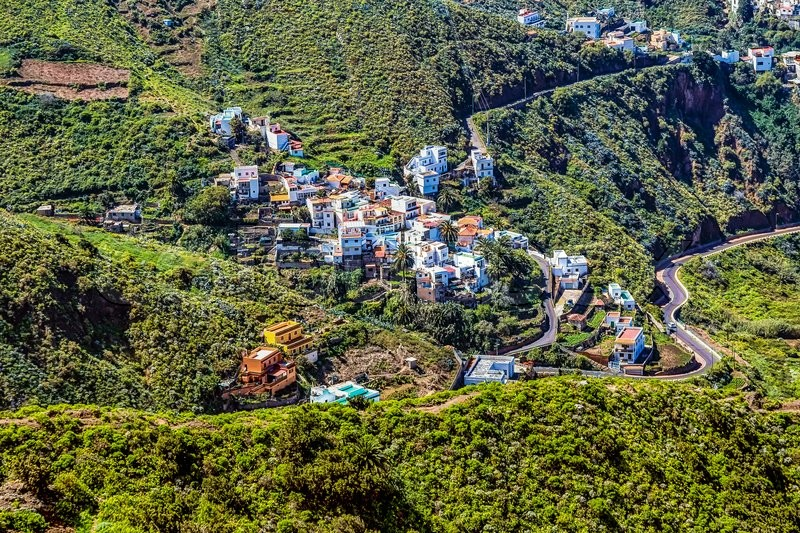 Small village buildings in green mountains valley on Tenerife Canary island, Spain, stock photo