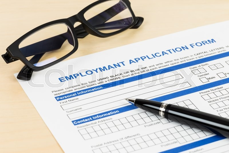 Employment application form with pen and glasses; form is mock-up, stock photo