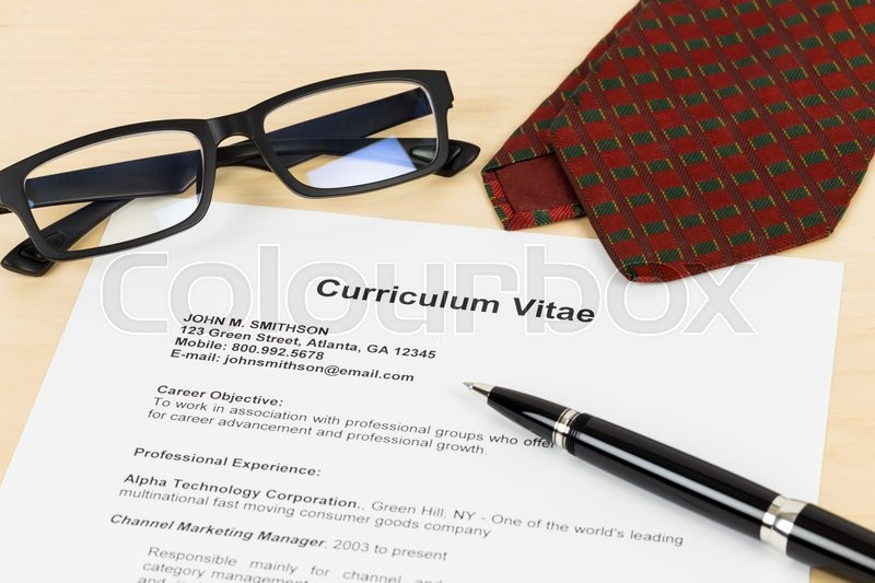 Curriculum vitae or CV with pen, glasses, and neck tie; concept job applying, stock photo