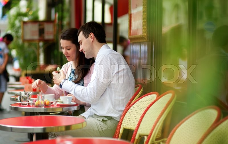 Happy couple eating macaroons in a Parisian outdoor cafe, stock photo