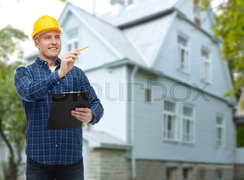 Repair, construction, building, people and maintenance concept - smiling male builder or manual worker in helmet with clipboard taking notes over living house background, stock photo