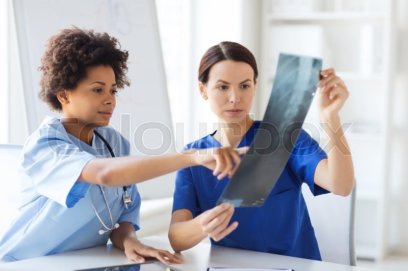 Radiology, surgery, people and medicine concept - female doctors looking to and discussing x-ray image at hospital, stock photo