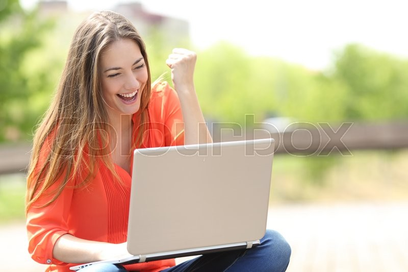 Euphoric woman searching job with a laptop in an urban park in summer, stock photo