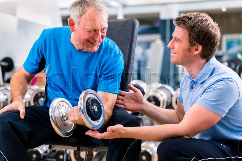 Senior man and trainer at exercise in gym with dumbbell weights, stock photo