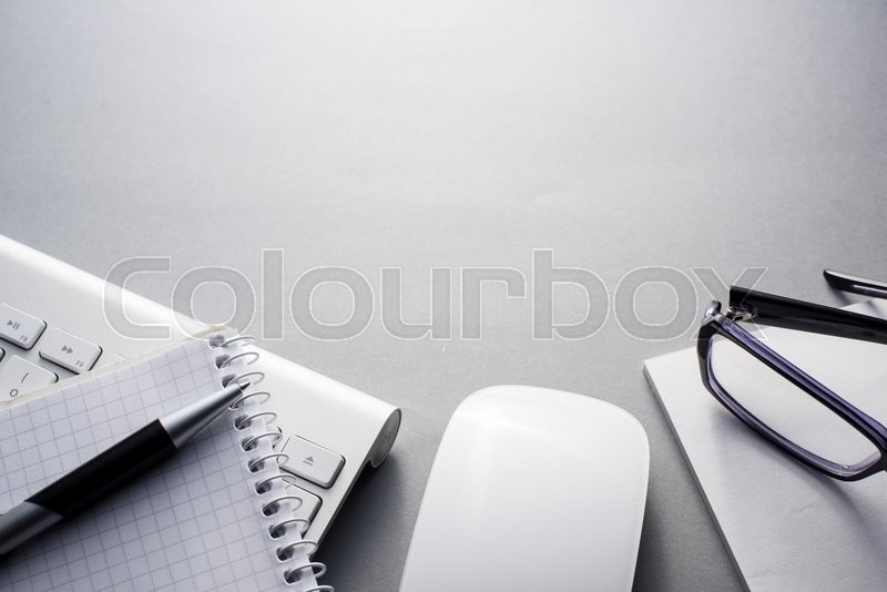 High Angle View of Mac Computer Keyboard and Mouse on Grey Desk with Note Book, Eyeglasses and Pen and Ample Copy Space, stock photo