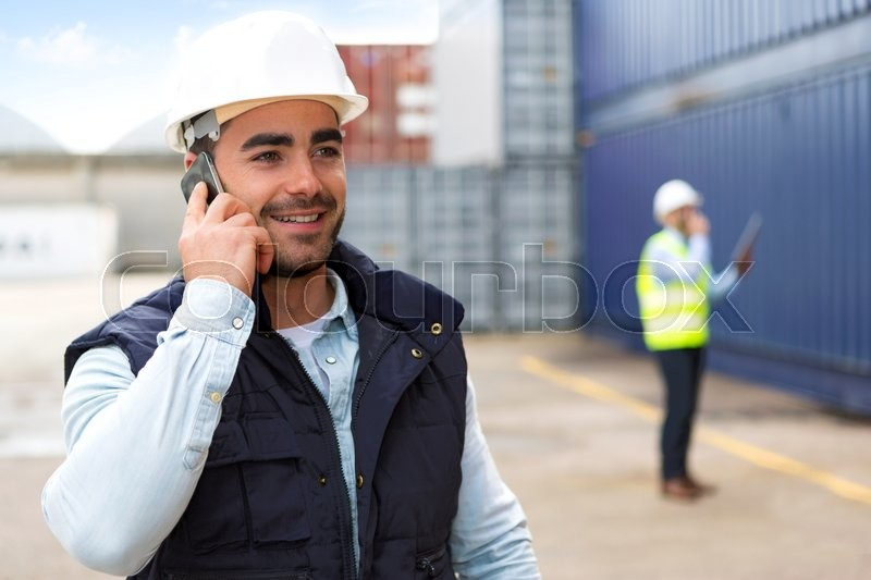 View of a Young Attractive docker using mobile phone at work, stock photo