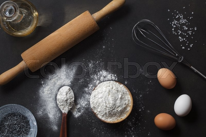 Flour and ingredients on black table. Top view, stock photo