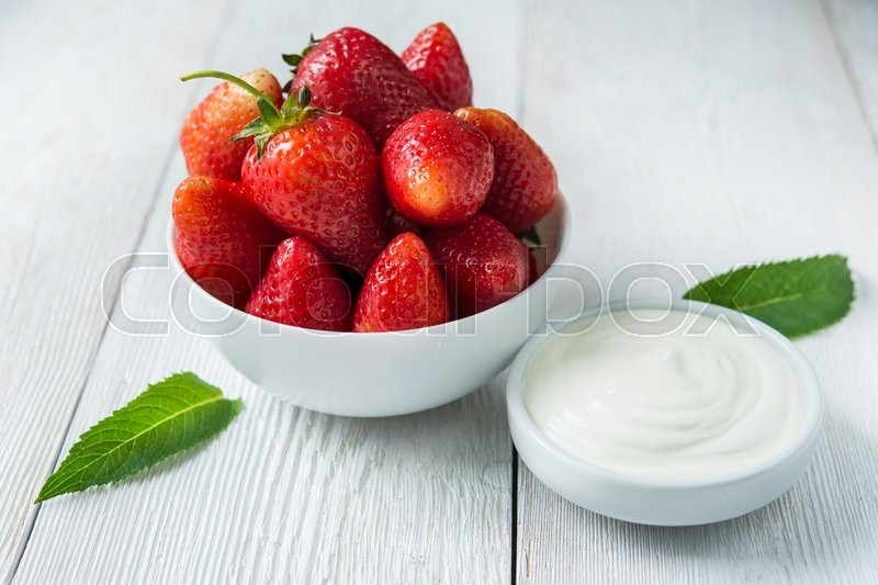 Fresh red strawberries with cream om white wood table. Easy dietary breakfast, stock photo