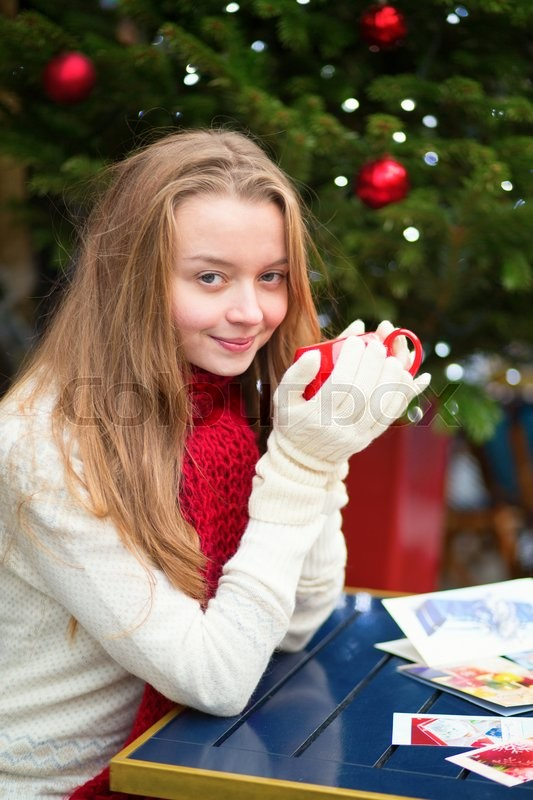 Girl drinking coffee and writing Christmas postcards in an outdoor Parisian cafe, stock photo