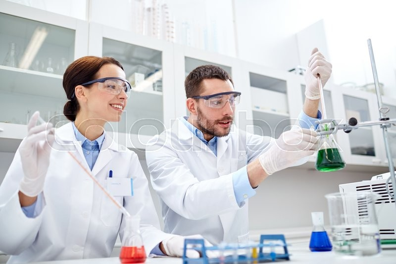 Science, chemistry, biology, pharmacy and people concept - young scientists with pipette and flask making test or research in clinical laboratory, stock photo