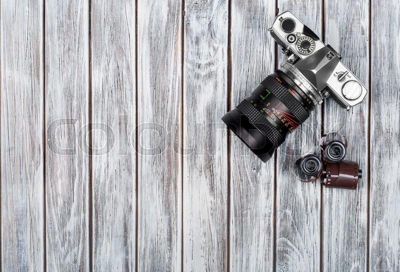 Old photo film rolls, cassette and retro camera on background. Vintage stylized, stock photo