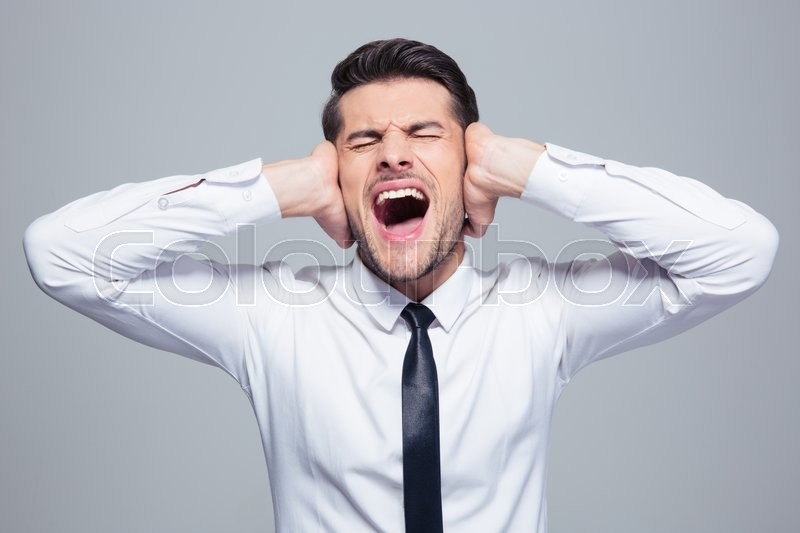 Businessman covering his ears and screaming over gray background, stock photo