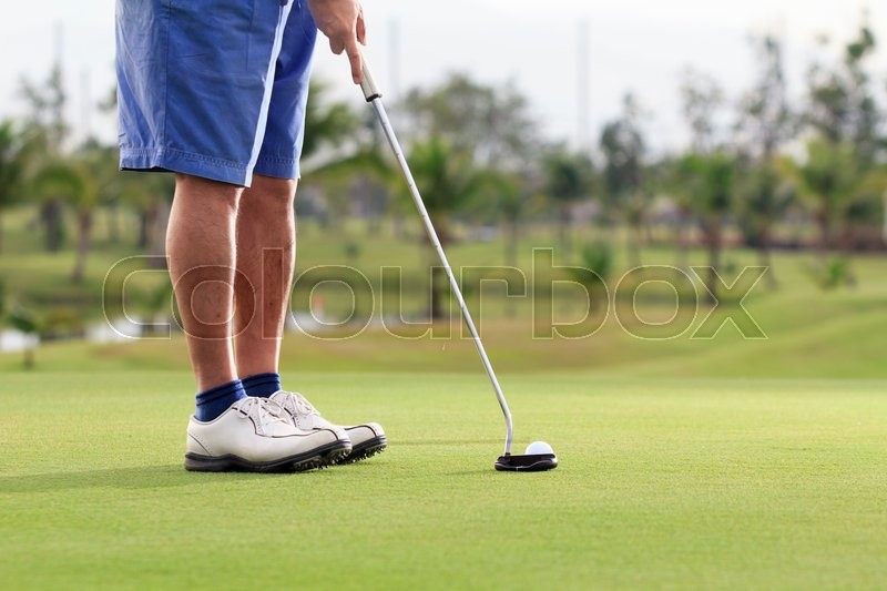 Golf player putting on the green, stock photo