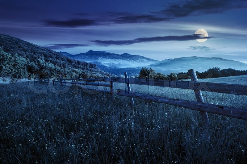 Rural landscape. fence on the hillside meadow shot with ultrawideangle lense. forest in fog on the mountain top at night in full moon light, stock photo