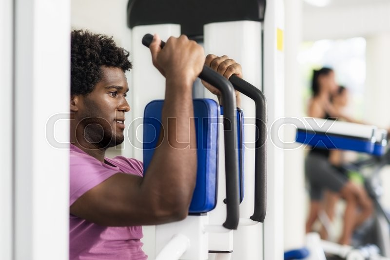 Young black man exercising pectoral muscles in fitness club, with people working out on cyclette in background, stock photo