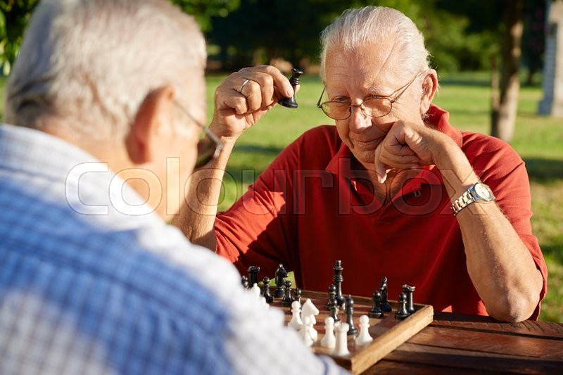 Active retired people, old friends and free time, two senior men having fun and playing chess at park. Head and shoulders, stock photo