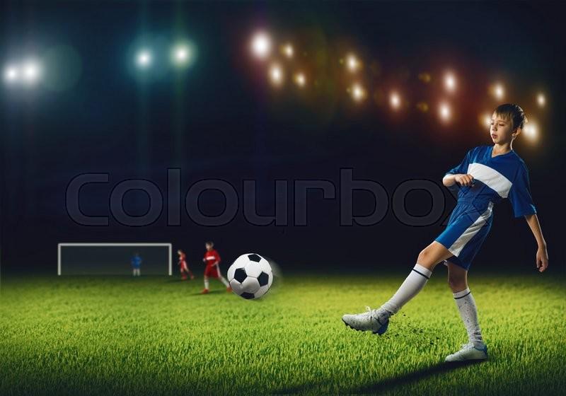 Excited boy football player at stadium kicking ball, stock photo